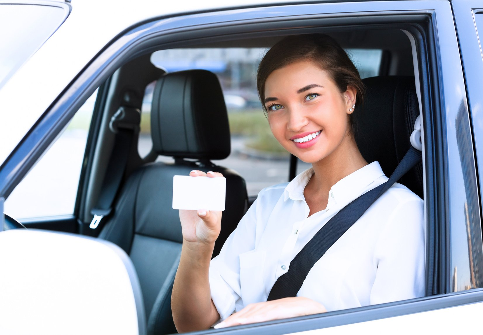 girl in a car showing an empty white card for your message