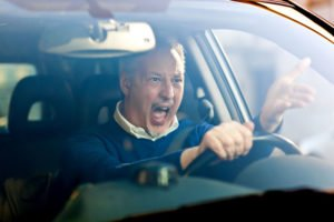 a man behind the wheel of a car and he is angry